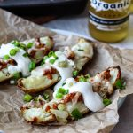 a photo of baked potato skins topped with tempeh bacon, cheese, sour cream, and green onion, served with an organic beer.