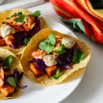 three tacos stuffed with gochujang tofu, sunbutter sauce, kimchi, cabbage, and cilantro.