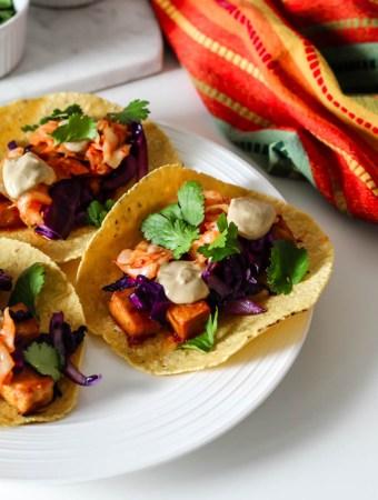 three tacos stuffed with gochujang tofu, sunbutter sauce, kimchi, cabbage, and cilantro.