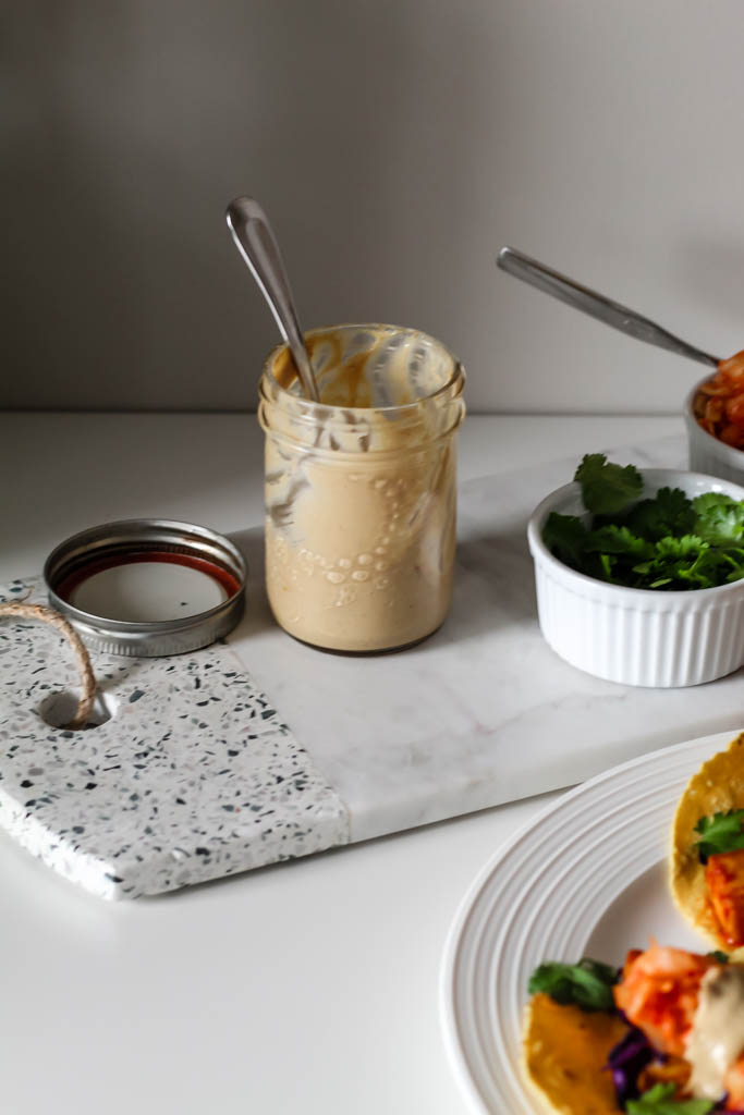 a jar of sunflower seed butter sauce with a spoon in it atop a decorative marble board. There is also a ramekin with cilantro and a container with kimchi in it.