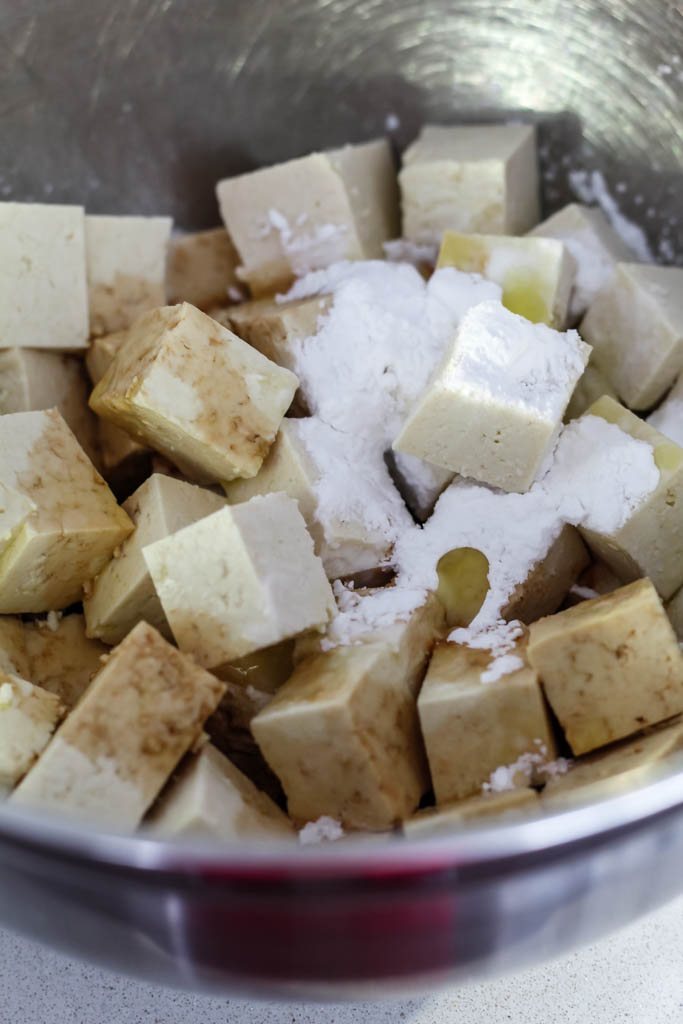 tofu cubes in a bowl topped with olive oil, tamari, and arrowroot.