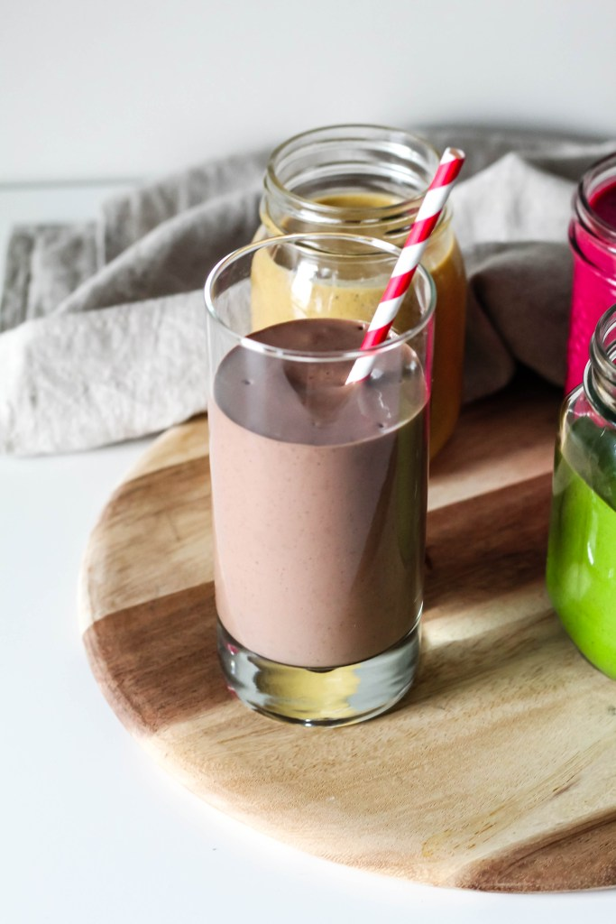 An image showing the peanut butter cup smoothie on a board surrounded by the other smoothies.