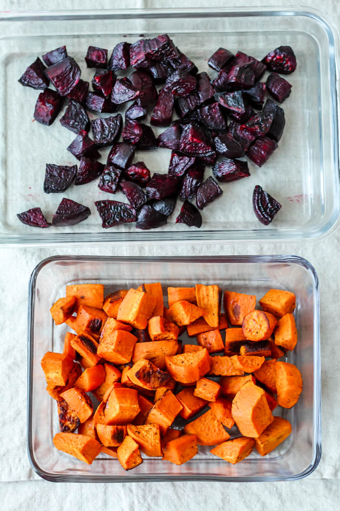 an overhead shot of roasted beets in one glass container and roasted sweet potatoes in another glass container.