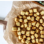 a pinterest graphic showing the overhead photo of crispy baked tofu on a plate with text that reads crispy baked tofu