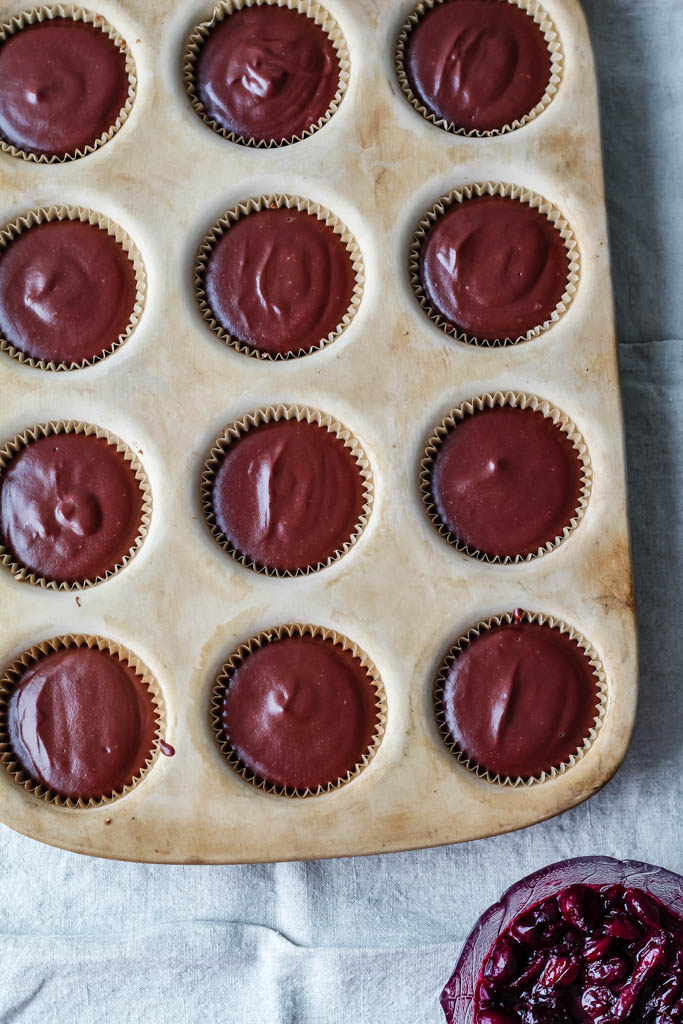 this photo shows the 12 no bake mini vegan chocolate cheesecakes in the muffin pan with the cherry compote right beside them.