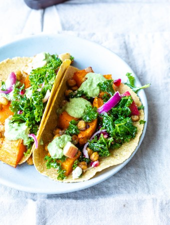 a fully dressed taco filled with squash and chickpeas on a blue plate.