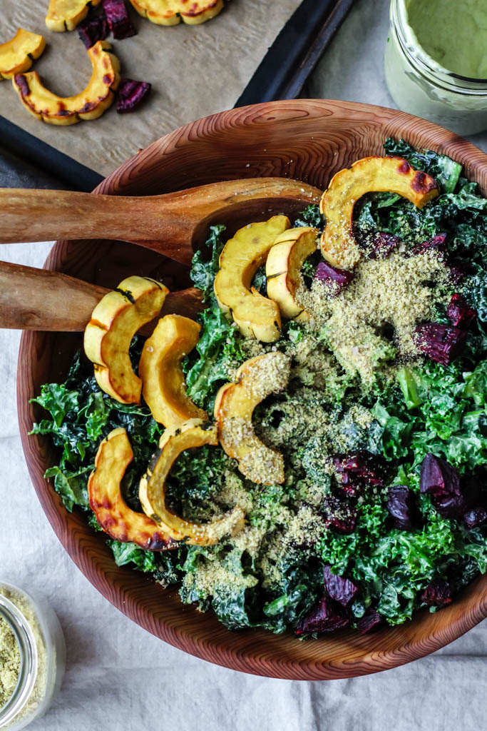 An overhead shot displaying a bowl of kale caesar salad topped with avocado and hemp dressing and roasted delicata squash, beets, and sunflower seed Parmesan.