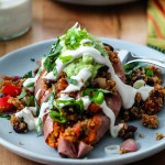 a straight on shot of a fully loaded stuffed sweet potato on a wooden backdrop