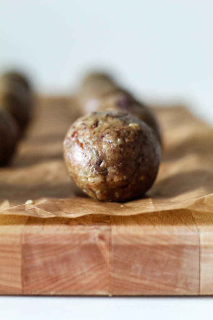a straight on shot of the energy balls on a wooden board