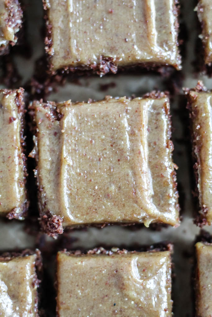 an overhead closeup shot of an oat flour almond butter brownie with brown salted date caramel frosting.