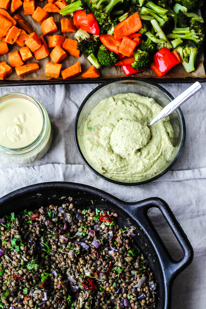 an overhead shot showing roasted sweet potato, broccoli, and red pepper on a baking sheet, the lemon tahini sauce, the hummus, and the marinated lentils in a cast iron skillet on a grey background.