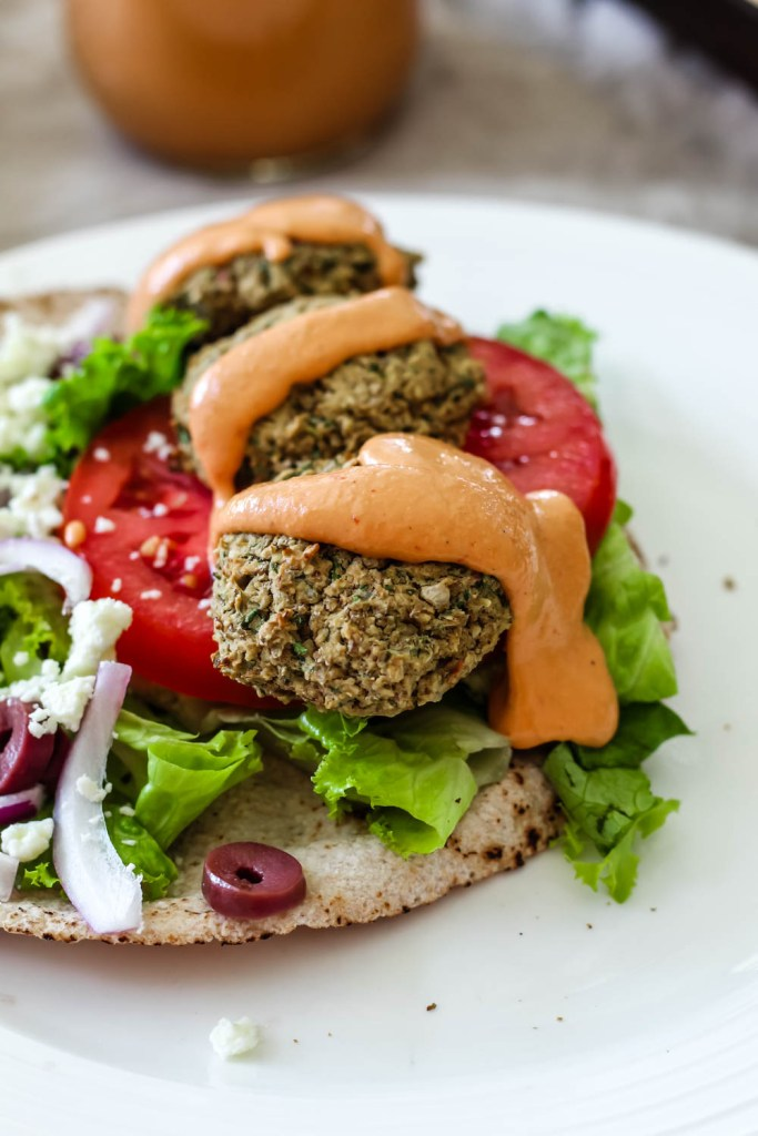 the lentil falafels on a loaded falafel pita topped with chipotle tahini sauce