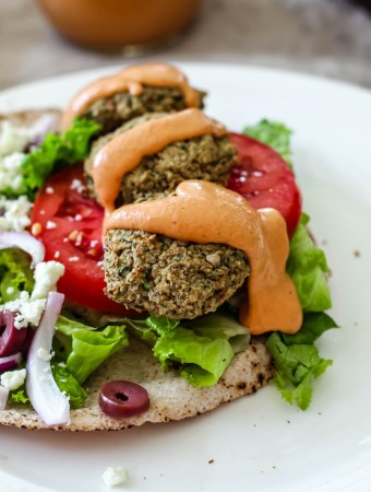 close up of lentil falafel pita with the sauce drizzle on top
