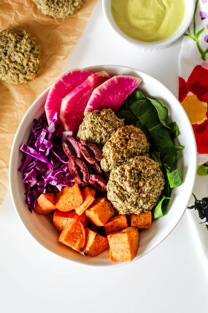 overhead shot of the falafel bliss bowl with a container of cashew sunshine sauce close by