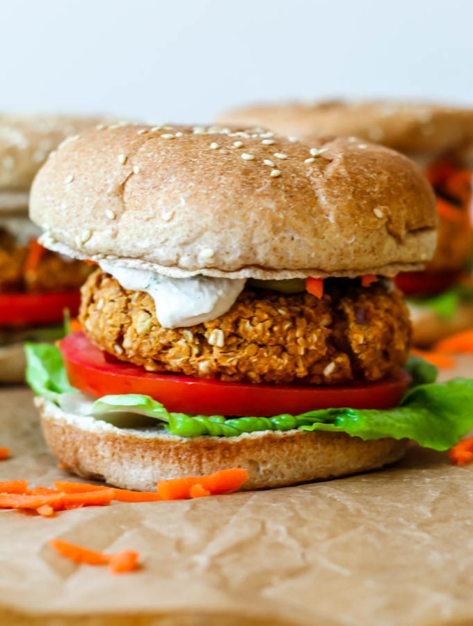 shot of a fully dressed buffalo chickpea burger on a sprouted grain bun