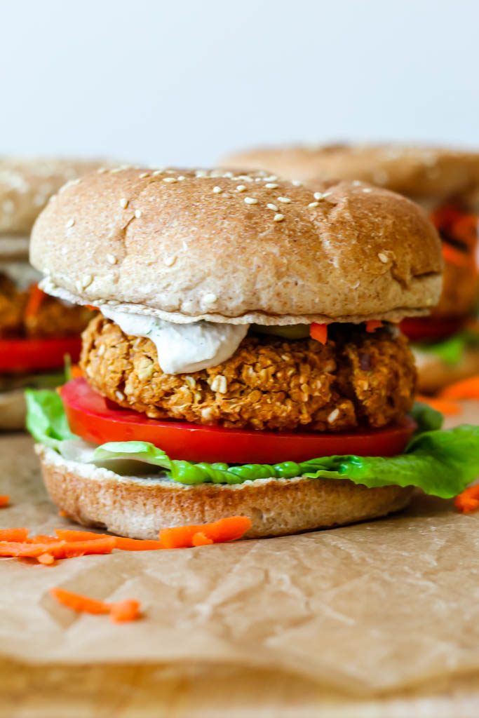 straight on shot of a fully dressed buffalo chickpea burger on a sprouted grain bun