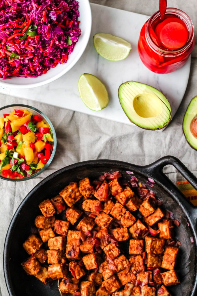 overhead shot of the barbecue tempeh, mango salsa, avocado, pickled radishes, and slaw