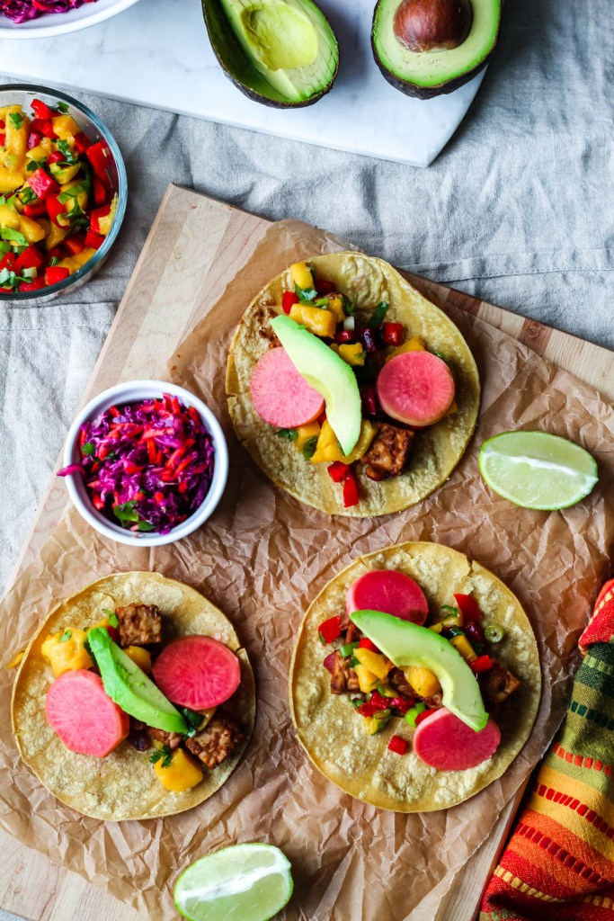 overhead shot of the tacos surrounded by mango salsa, slaw, avocado