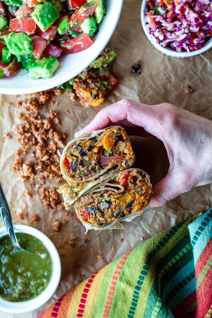 overhead shot of the burrito being held in a hand with a sheet of crumpled parchment paper in the background.