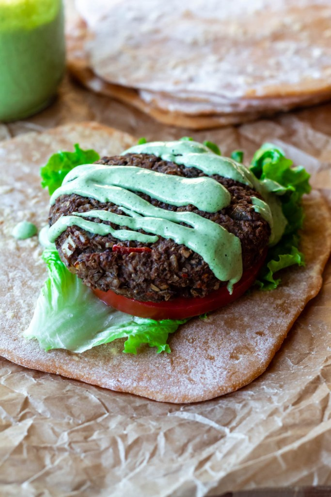 straight on shot of a lentil walnut burger on a tortilla topped with mint lime hemp avoado dressing