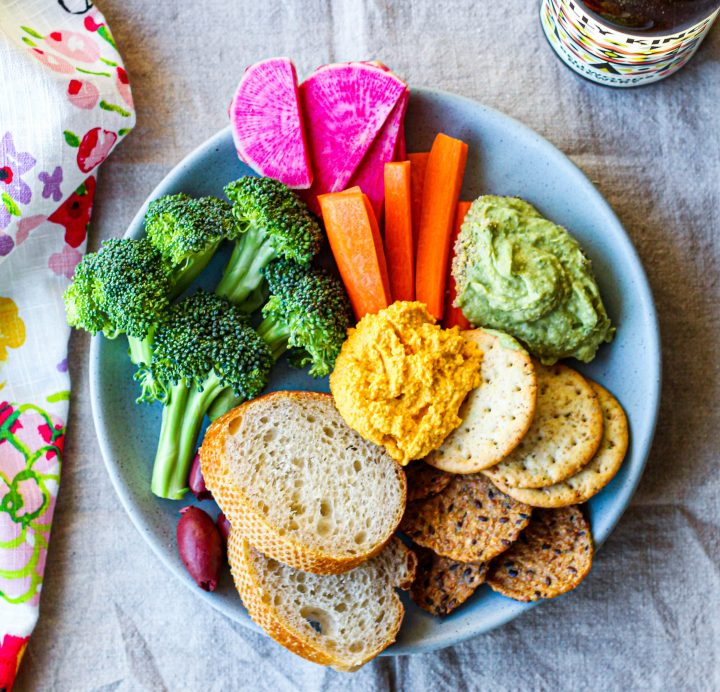 an overhead shot of a vegan snack plate with crackers, baguette, hummus, cashew carrot dip, and vegetables, with a bottle of craft beer