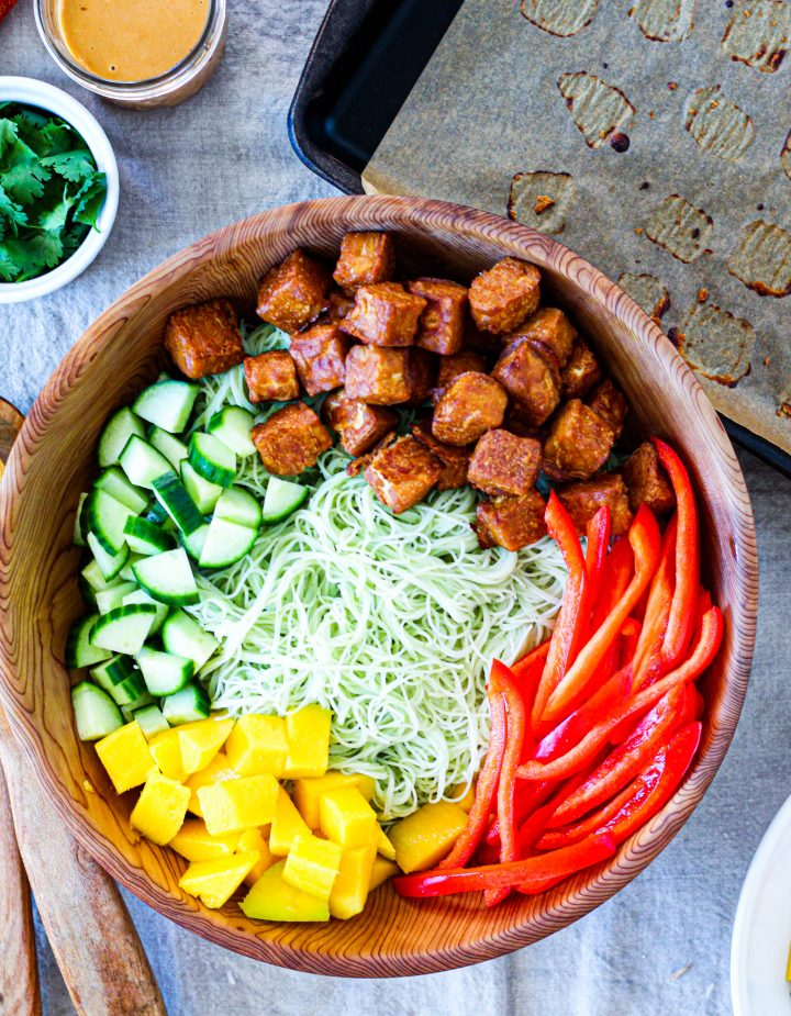 an overhead shot of the peanut tempeh salad in a wooden bowl with the tempeh cubes, cucumber, peppers, and mango arranged over top of the rice noodles.
