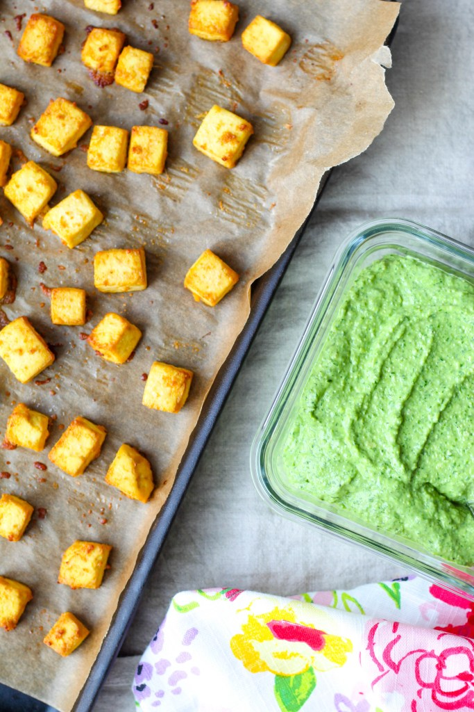 an overhead shot of the tofu on a baking sheet accompanied by the green goddess pesto in a container