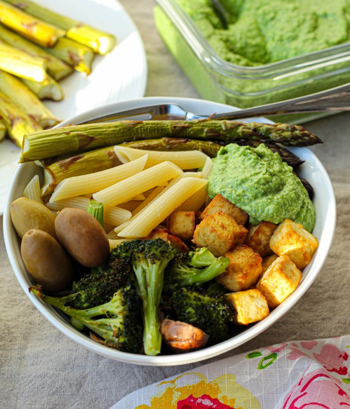 a straight on shot of the green goddess pesto bowls in soft, summery light. Roasted broccoli, asparagus, olives, cheesy baked tofu, pasta, and green goddess pesto are arranged in a white bowl.