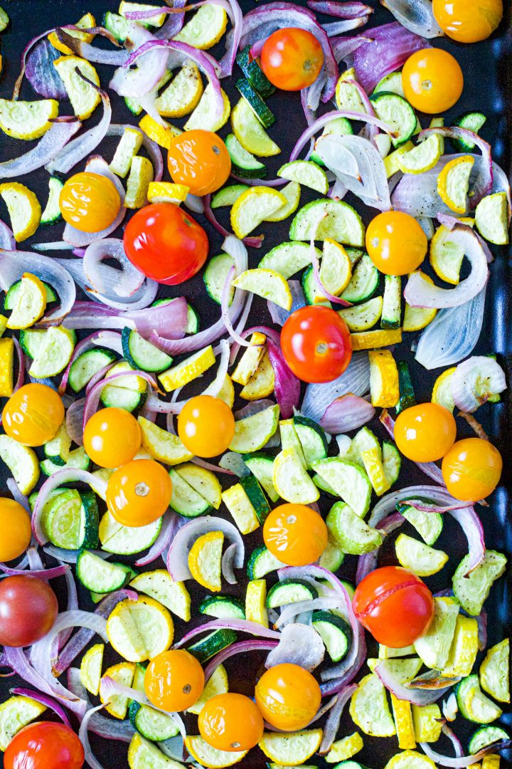 overhead shot of the roasted zucchini and tomatoes on a baking sheet
