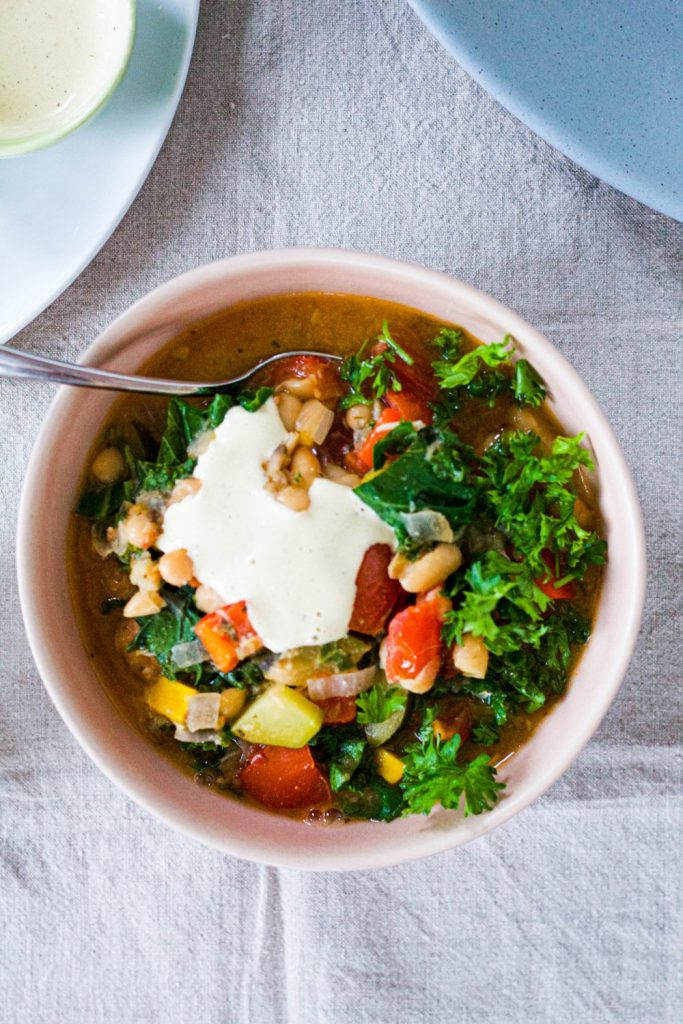 overhead shot of a bowl of the stew topped with lemon tahini sauce