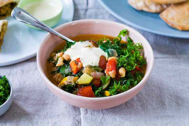 garden vegetable stew in a bowl with lemon tahini sauce on top
