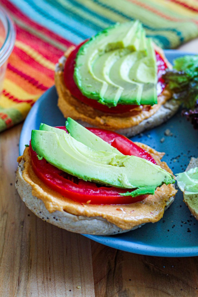 close up of a bagel half with hummus, tomato, and avocado on it