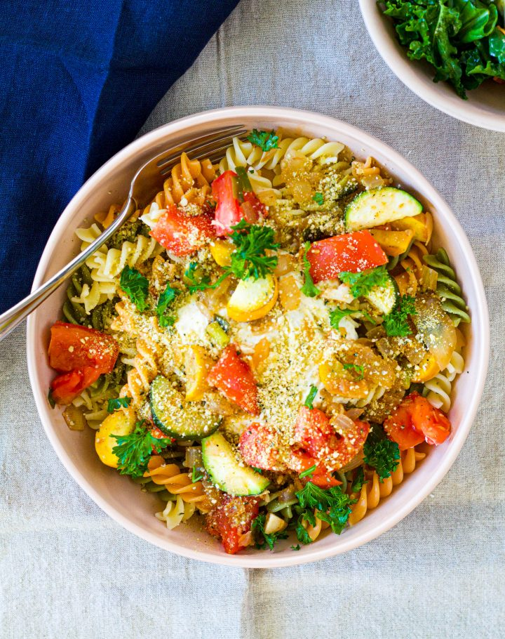 overhead shot of a bowl of the lemon ricotta pasta on tricoloured pasta noodles topped with tomatoes and zucchini