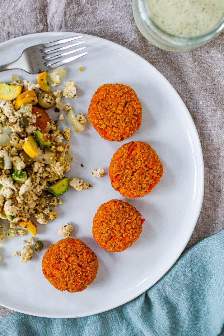 overhead shot of the quinoa cakes on a white plate with tofu scramble