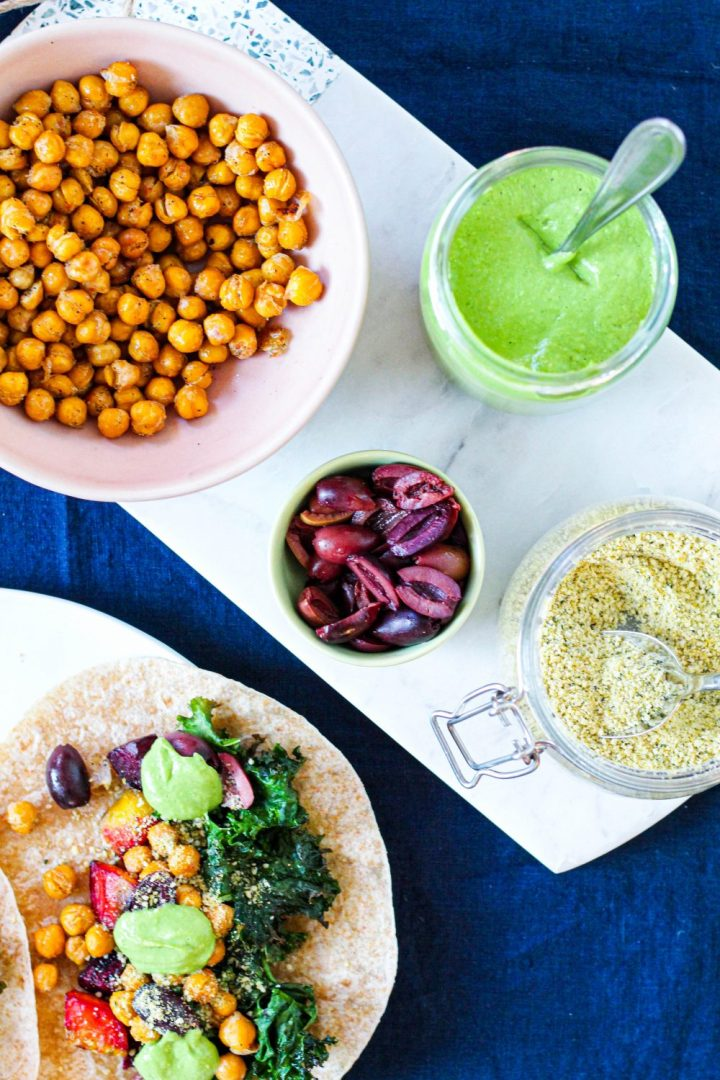 overhead image of the avocado sauce, roasted chickpeas, olives, cashew parmesan, and the edge of a taco