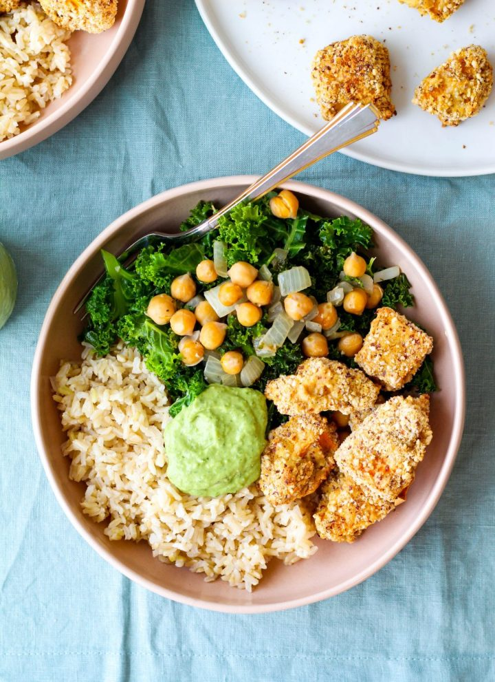 overhead shot of the bowl with squash, brown rice, kale, chickpeas, and avocado sauce