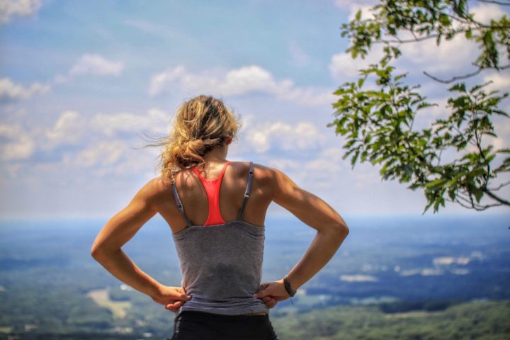 woman standing on a small peak overlooking green space