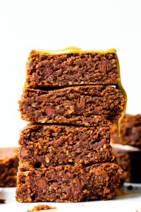 straight on shot of a stack of four brownies on a white plate