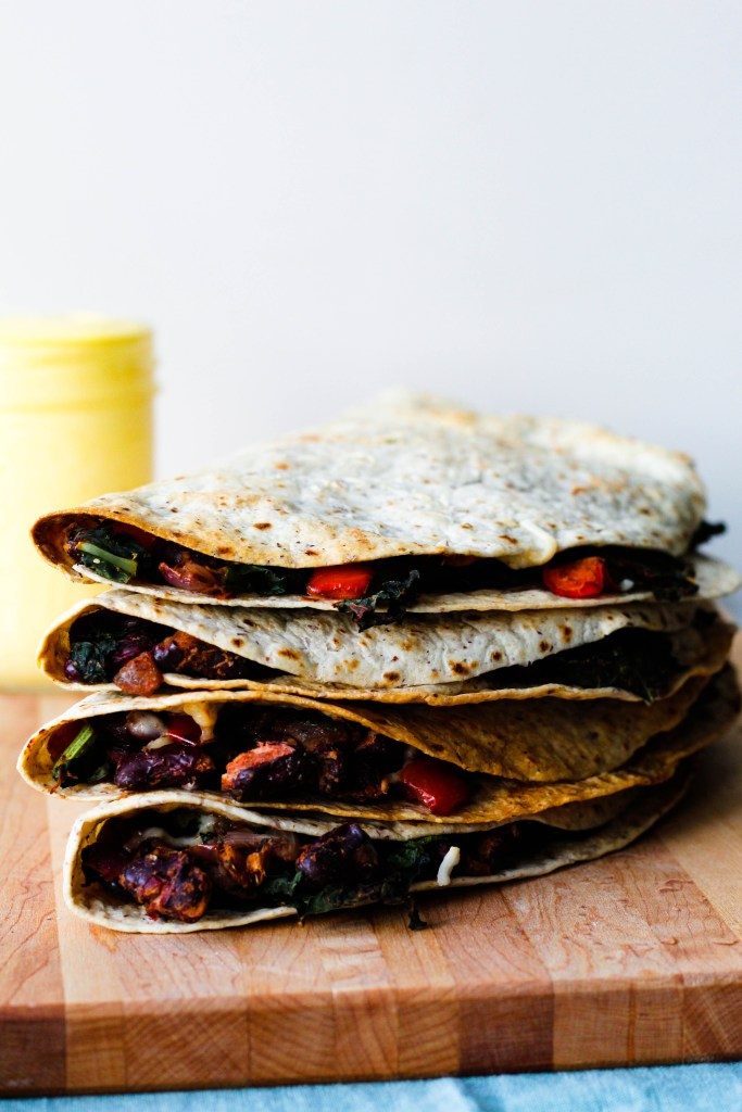 straight on shot of a stack of four of the quesadillas on a wooden board with the mango aioli in the background