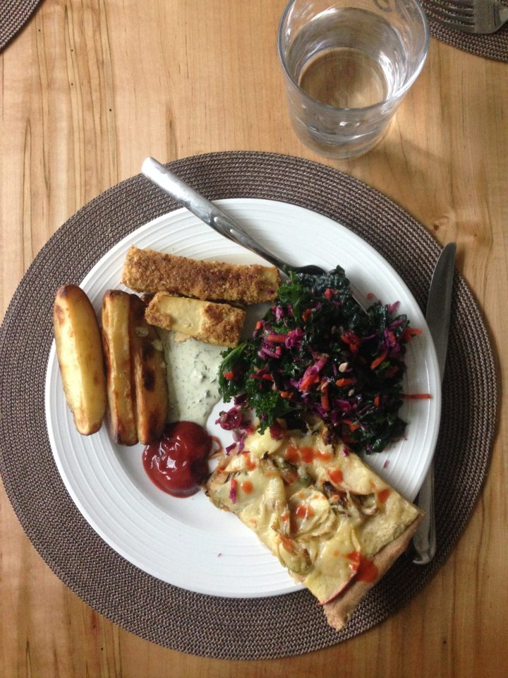 overhead shot of my lunch plate with a slice of homemade pizza, tofu nuggets, oven fries, and kale salad
