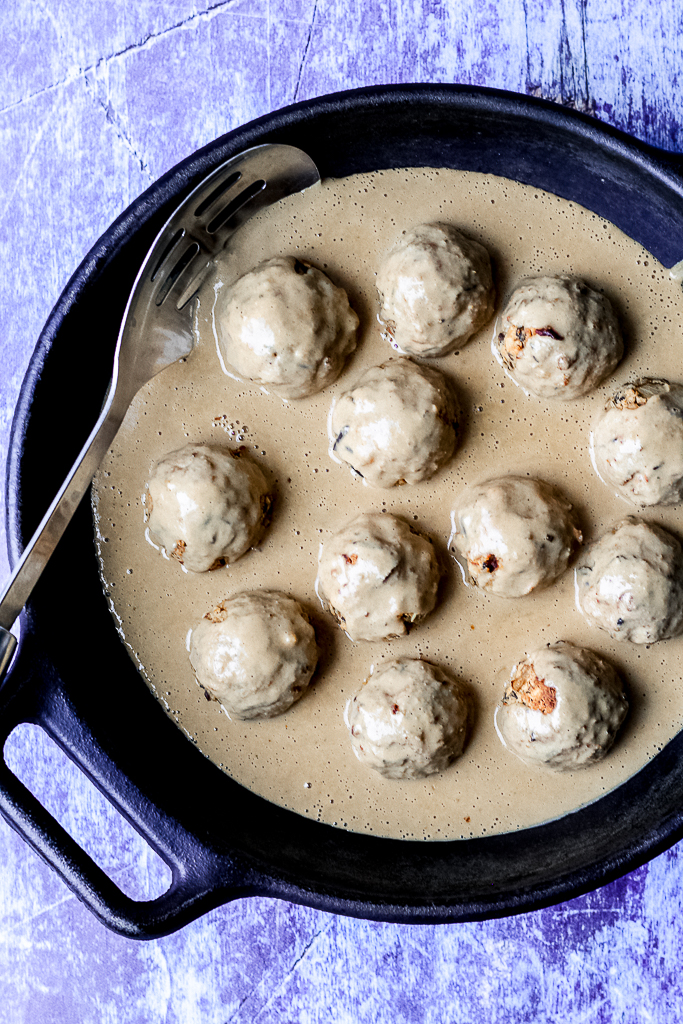 overhead shot of the meatballs and gravy in a cast iron skillet on a blue backdrop