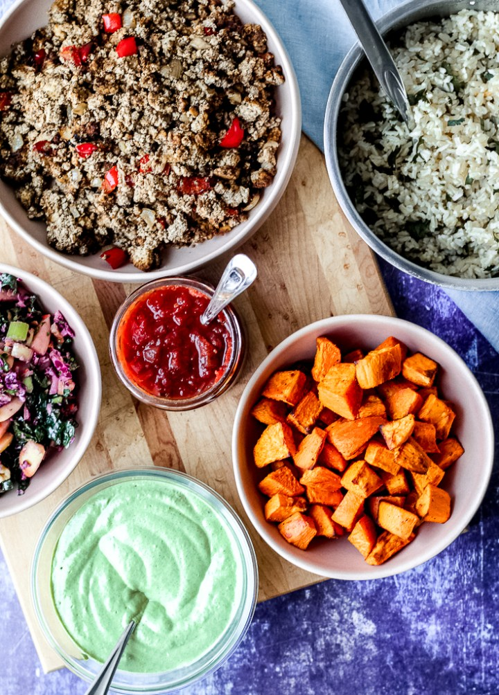 overhead shot of all the fillings- jerk tofu crumbles, avocado sauce, sweet potato, slaw, salsa, and cilantro lime rice- in dishes, against a blue backdrop