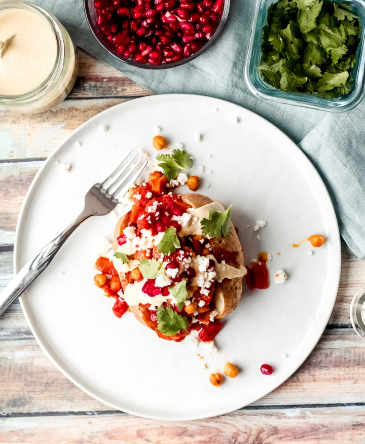 Moroccan chickpea baked potato on a plate with cilantro, pomegranate, and lemon tahini sauce around the plate