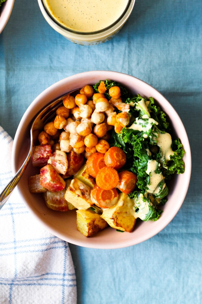 overhead shot of a bowl with roasted potato, beets, carrots, and steamed kale, roasted chickpeas, and nutritional yeast dressing drizzled over top