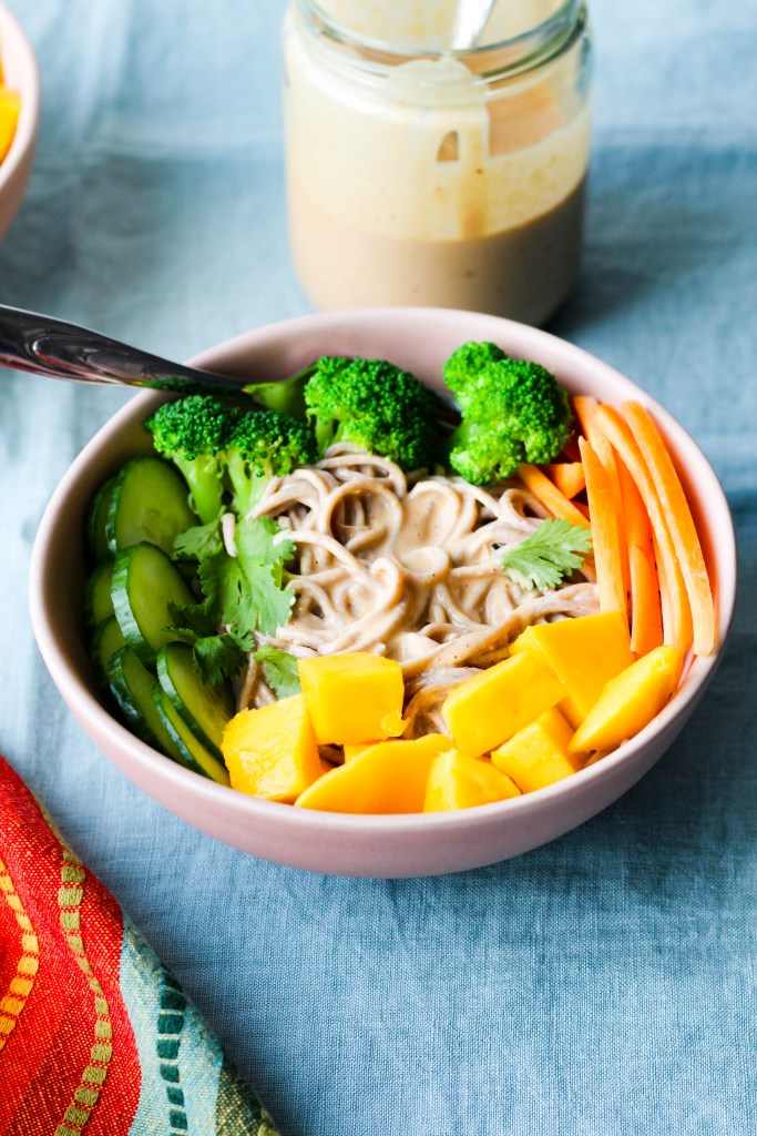 straight on shot of a bowl of the saucy peanut butter noodles topped with the veggies and mango