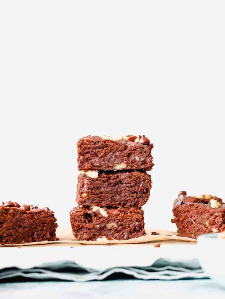 straight on shot of a stack of three brownies on a marble board against a blue towel
