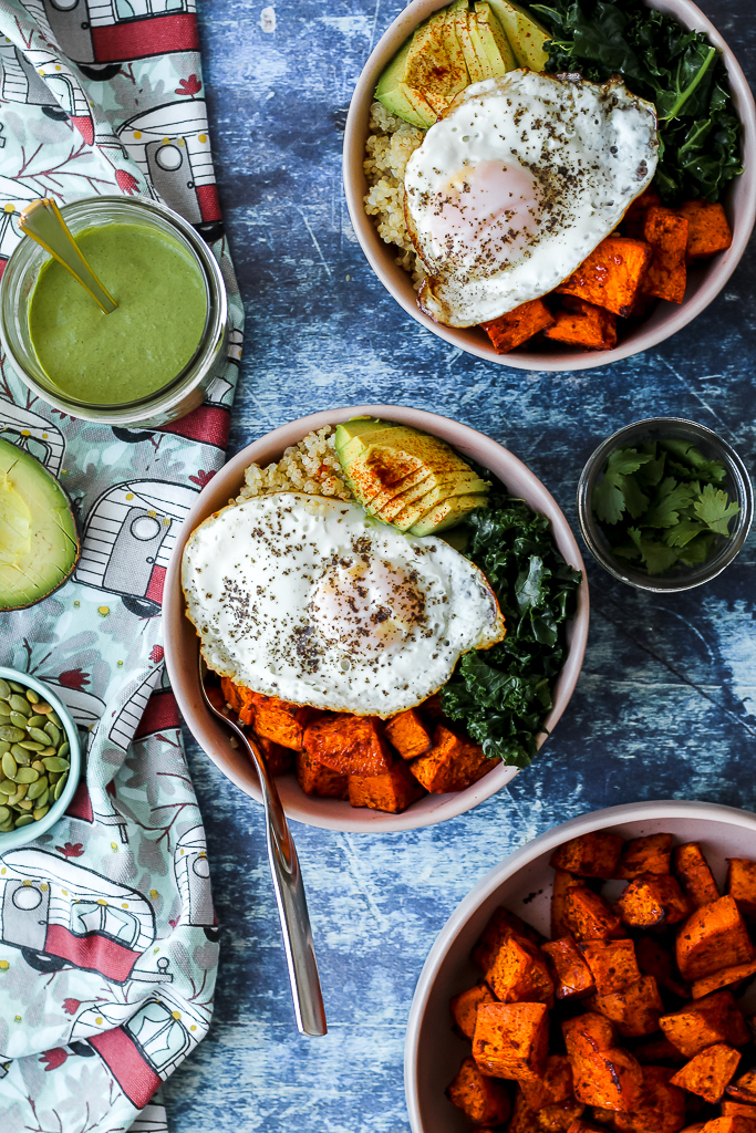 overhead shot of two bowls filled with quinoa, roasted sweet potato, eggs, greens, and avocado