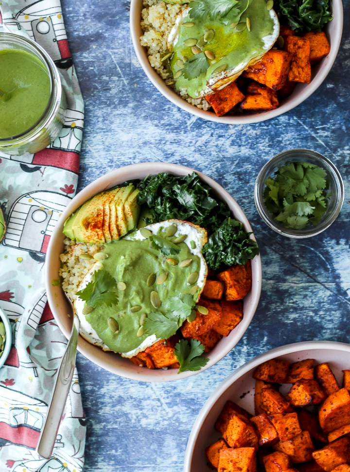 overhead shot of the greens, eggs, and yams bowls on a blue backdrop