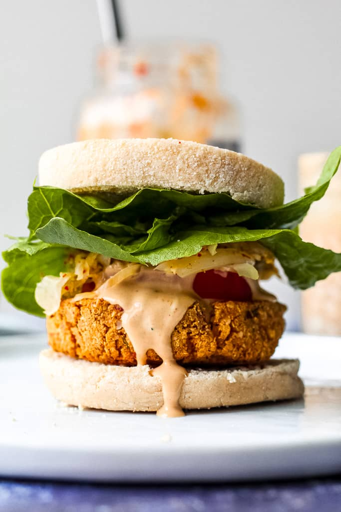 straight on shot of a fully dressed tofu burger on a white plate