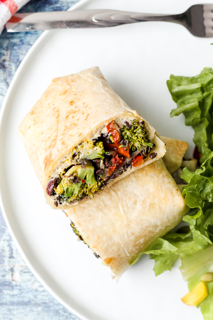 close up overhead shot of a broccoli lentil burrito on a plate with some salad on the side